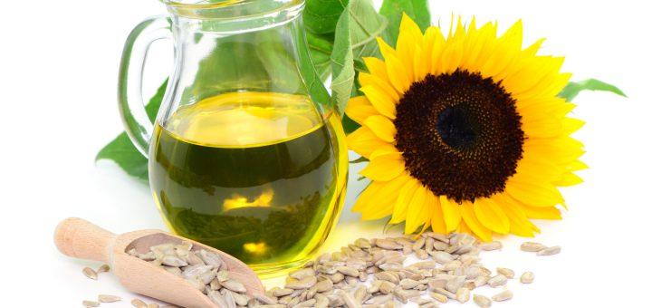 Kwiat słonecznika i dzbanek z zawartością oleju