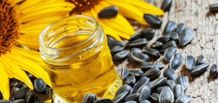 Odkręcony słoik z zawartością oleju w otoczeniu nasion